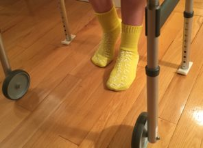 person wearing non-slip socks on hard wood floors and using a walker
